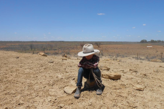 Boy in Drought in Queensland (Image from https://www.abc.net.au/news/2016-05-25/boy-sitting-on-drought-affected-land-in-queensland/7444406)